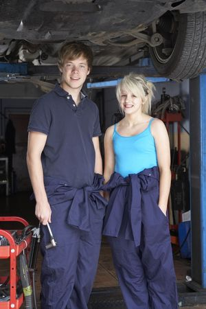 Mechanic and apprentice working on car photo