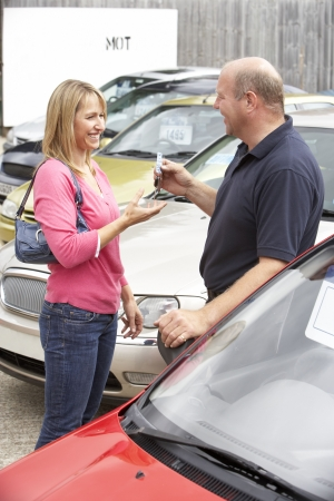 new car lot: Young woman collecting new car