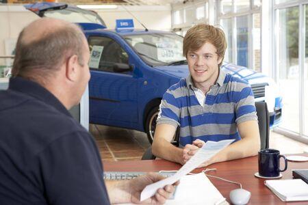 Młody mężczyzna wypełnianie słuchaczowi w salon samochodowy
