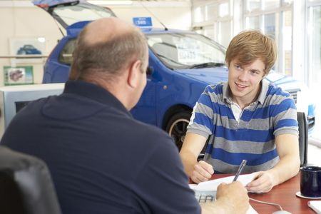 Young man filling in paperwork in car showroom photo