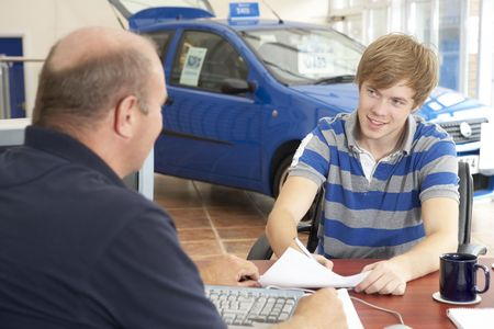 a lot of money: Young man filling in paperwork in car showroom Stock Photo