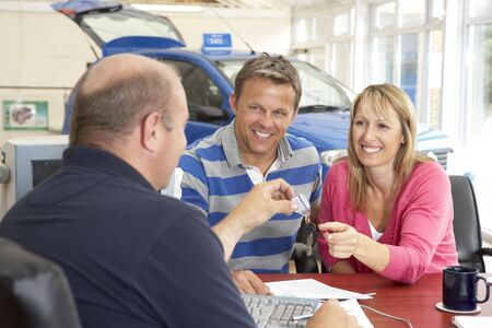 new car lot: Couple filling in paperwork in car showroom
