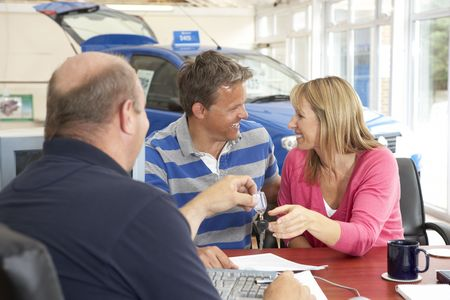gastos: Couple filling in paperwork in car showroom
