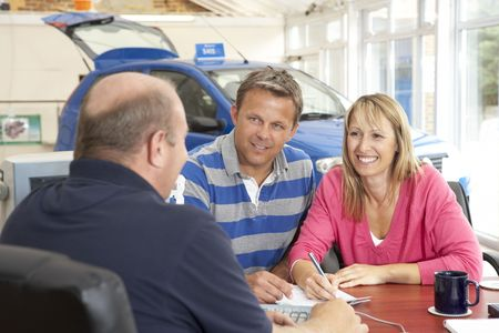 Couple filling in paperwork in car showroom photo