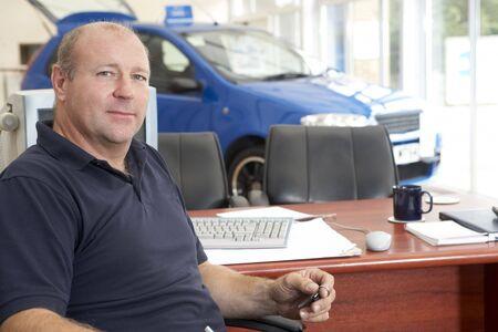 Car salesman sitting in showroom photo