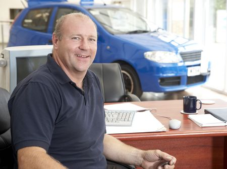 Car salesman sitting in showroom smiling photo