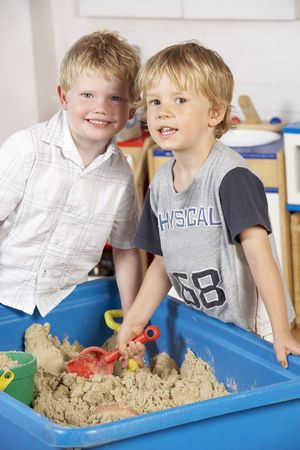 four year olds: Two Young Boys Playing Together in Sandpit  Stock Photo