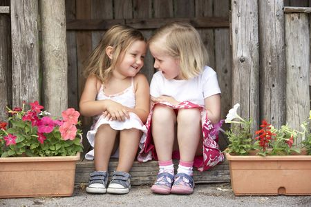 playgroup: Two Young Girls Playing in Wooden House Stock Photo