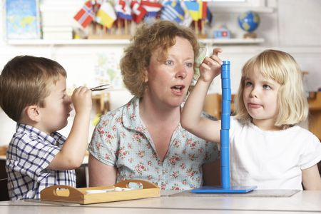 Adult Helping Two Young Children at Montessori/Pre-School Stock Photo - 5633389