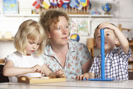 Adult Helping Two Young Children at Montessori/Pre-School Stock Photo - 5633492