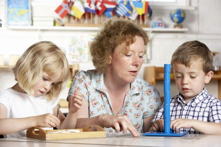 Adult Helping Two Young Children at Montessori/Pre-School Stock Photo - 5633521