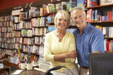 small: Couple running bookshop Stock Photo