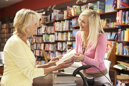 shop assistant: Female customer in bookshop Stock Photo