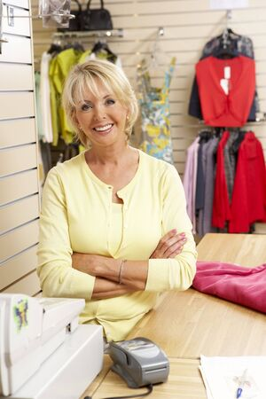aged business: Female sales assistant in clothing store