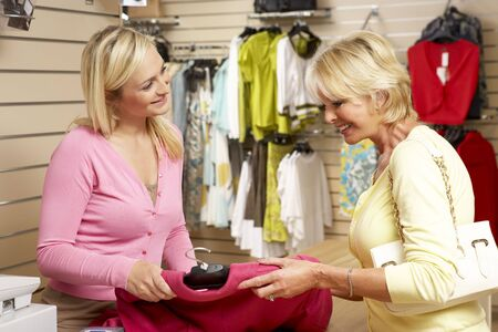 store clerk: Sales assistant with customer in clothing store Stock Photo