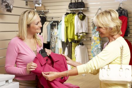 sales assistant: Sales assistant with customer in clothing store Stock Photo