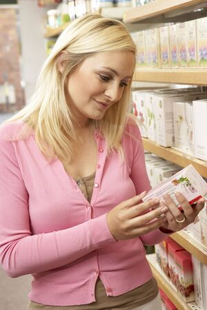 health food store: Female customer buying herbal tea