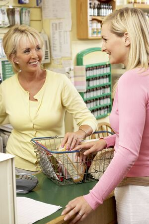 checkout stand: Sales assistant with customer in health food store Stock Photo