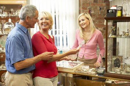 salesperson: Couple shopping in antique shop Stock Photo