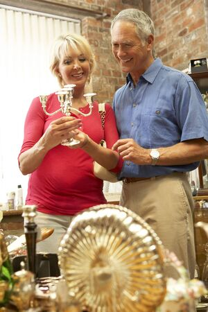 antiques: Middle aged couple shopping for antiques