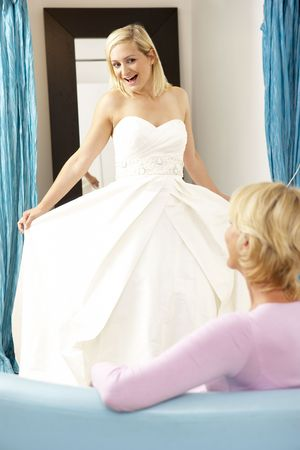 Bride trying on wedding dress with sales assistant photo