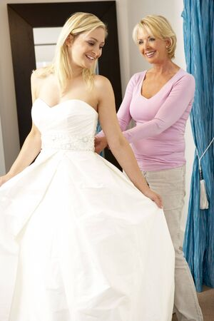 Bride trying on wedding dress with sales assistant Stock Photo - 5633121