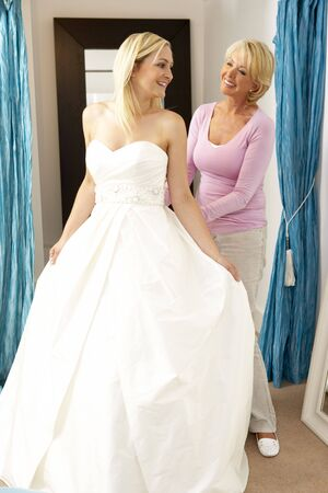 fitting: Bride trying on wedding dress with sales assistant