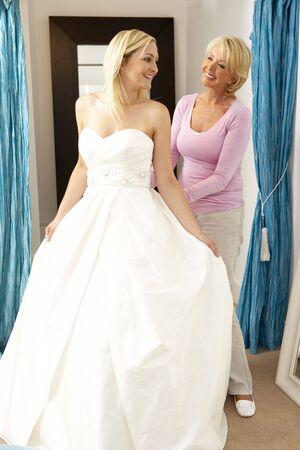 changing clothes: Tratando en el vestido de novia de la boda con la asistente de ventas