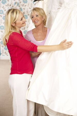 Bride trying on wedding dress with sales assistant Stock Photo - 5633077