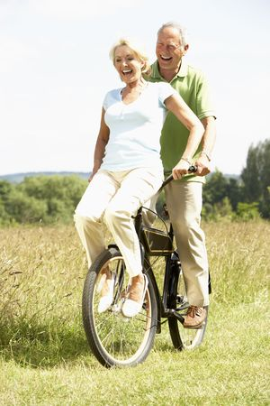 active couple: Mature couple riding bike in countryside Stock Photo