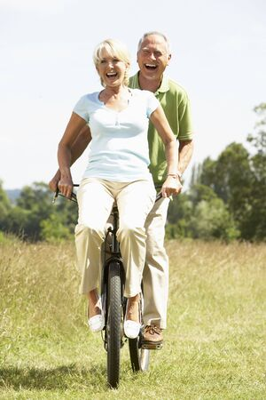 countryside loving: Mature couple riding bike in countryside Stock Photo