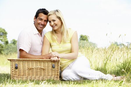 Young couple having picnic in countryside photo
