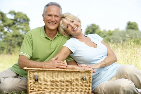 Mature couple having picnic in countryside photo