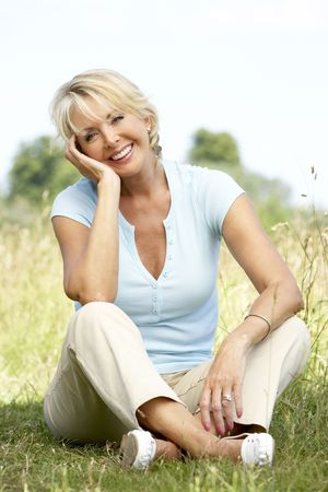 baby boomer: Portrait of mature woman sitting in countryside
