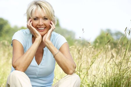 the fifties: Portrait of mature woman sitting in countryside