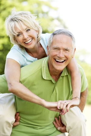piggyback: Mature couple having fun in countryside Stock Photo