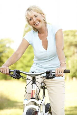 baby boomer: Portrait of mature woman riding cycle in countryside Stock Photo