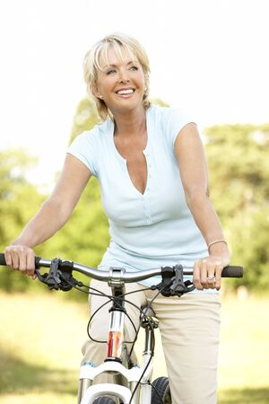 Portrait of mature woman riding cycle in countryside Stock Photo