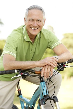 baby boomer: Portrait of man riding cycle in countryside