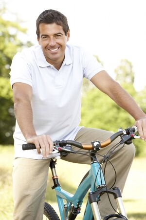 Young man riding bike in countryside Stock Photo - 5633215