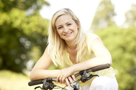 Young woman riding bike in countryside photo