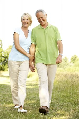 Mature couple walking in countryside photo