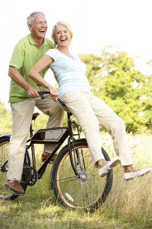 mature couple: Mature couple riding bike in countryside Stock Photo