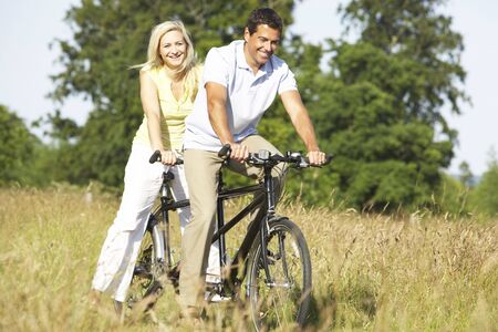 Couple riding tandem in countryside photo