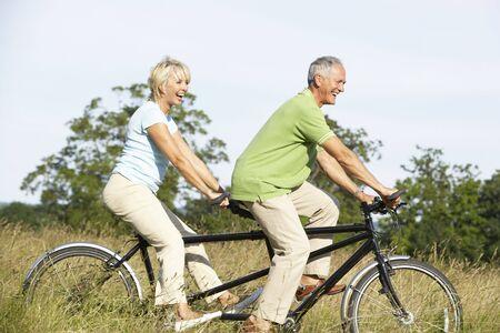 riding: Mature couple riding tandem