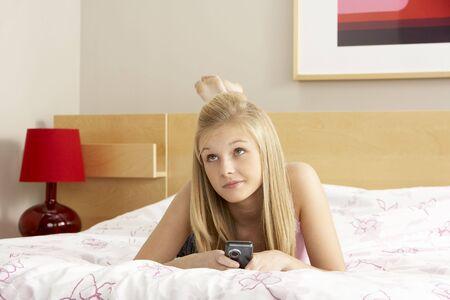 Teenage Girl In Bedroom With Mobile Phone photo