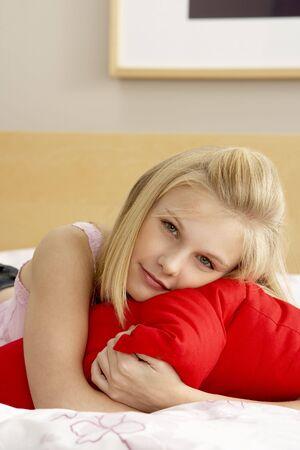 Teenage Girl In Bedroom Hugging Pillow photo