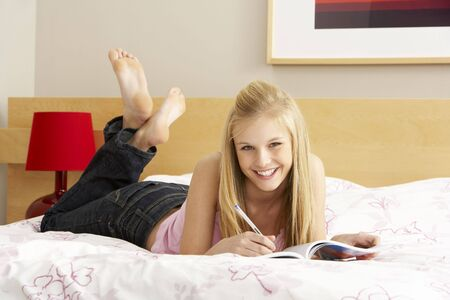 Teenage Girl Writing In Diary In Bedroom Stock Photo - 6127727