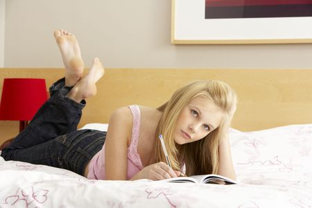 Teenage Girl Writing In Diary In Bedroom photo