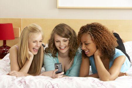 chicas adolescentes: Grupo de tres ni�as adolescentes mediante el tel�fono en la habitaci�n